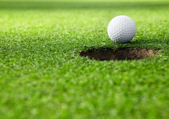 close-up of golf ball at the hole