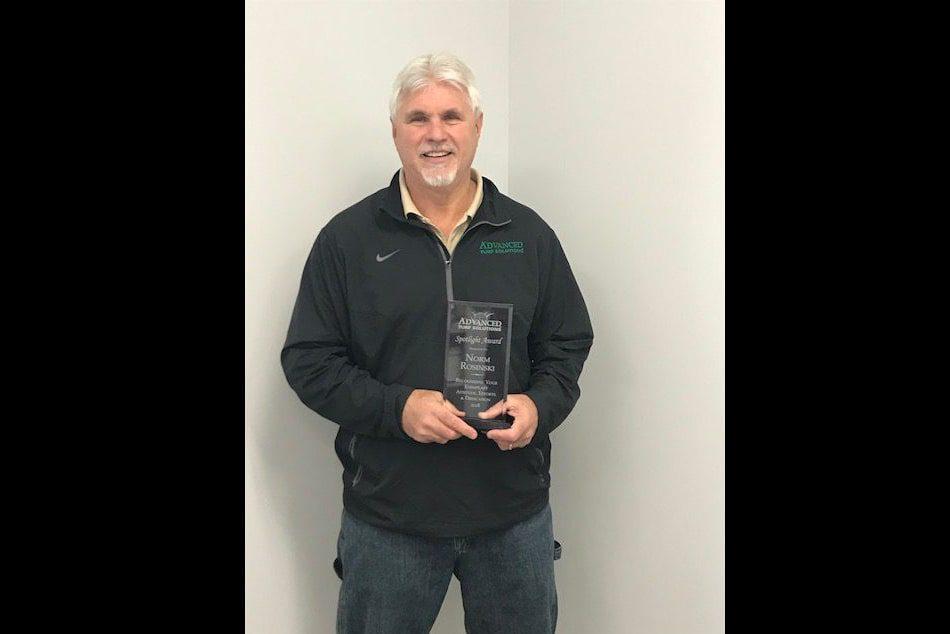 norm rosinkski holding his award smiling for portrait