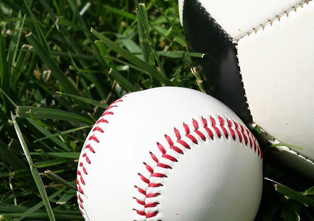 baseball and soccer ball sitting on a field