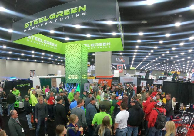 tons of people standing around Steel Green manufacturing tent at venue