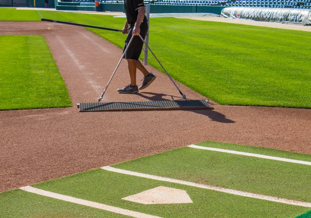 close up of home plate and gentleman leveling the dirt in the infield