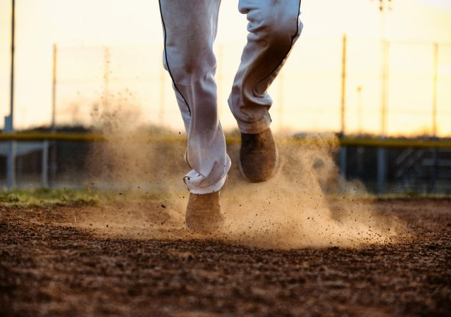 Baseball player feet running to base on field, dirt and dust moving from action of athlete