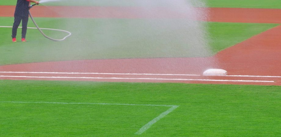 Person using hose to water infield of baseball field