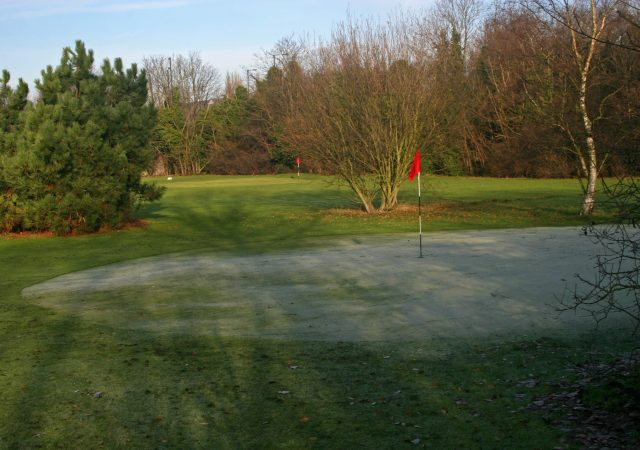 golf greens with red flag and dusting of snow